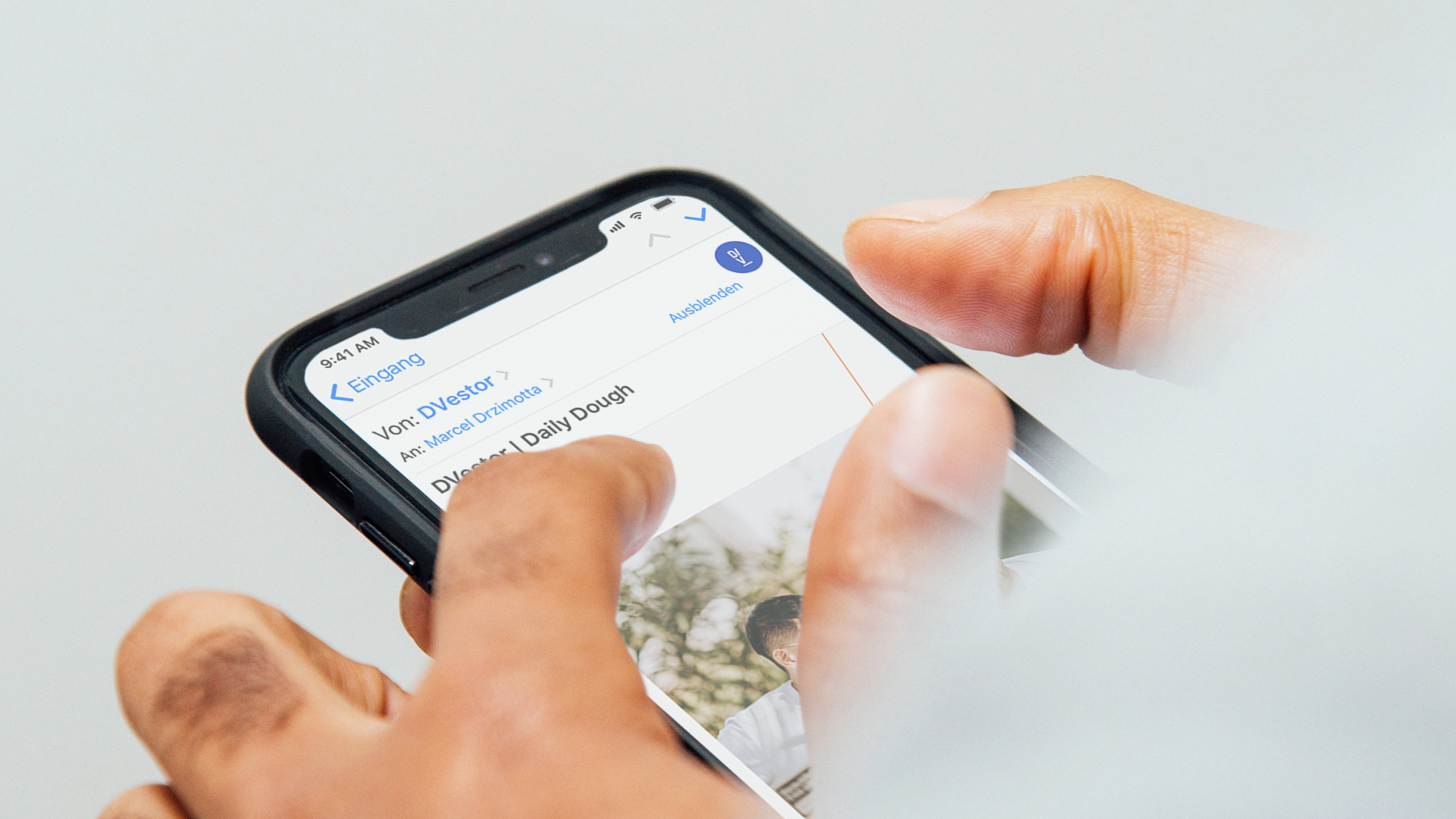 Mann hält iPhone und betrachtet DVestor Newsletter.