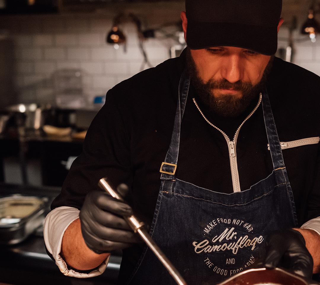 Mr. Camouflage Inhaber beim Kochen und trägt gebrandete Schürze.